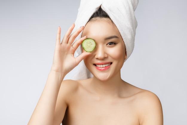 Beeld van de de huidzorg van schoonheids het jonge aziatische vrouwen met komkommer op witte studio als achtergrond.