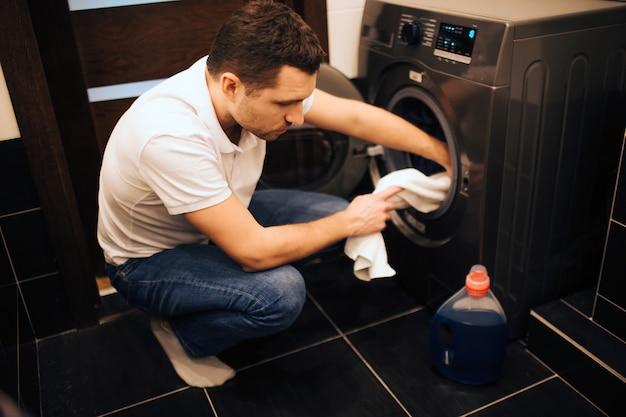 Beeld van de ernstige zekere mens die sommige kleren zetten in wasmachine.