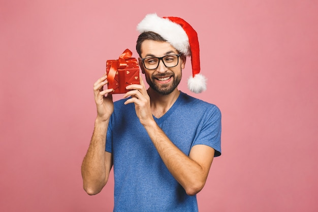 Beeld van de gelukkige jonge mens die de hoed van kerstmissanta dragen status geïsoleerd over roze de giftdoos van de muurholding.