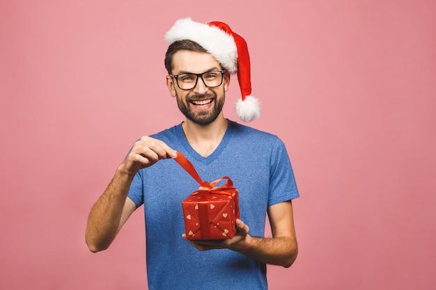 Beeld van de gelukkige jonge mens die de hoed van kerstmissanta dragen status geïsoleerd over roze de giftendoos van de muurholding.