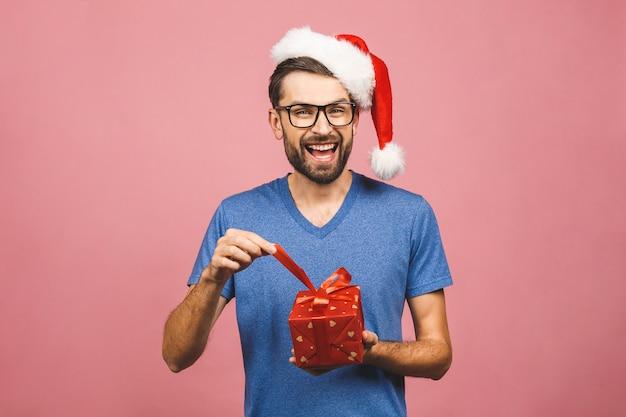 Beeld van de gelukkige jonge mens die de hoed van kerstmissanta status dragen geïsoleerd over roze de giftendozen van de muurholding.