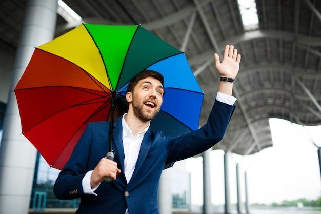 Beeld van de jonge bont paraplu die van de zakenmanholding hoogte-vijf tonen