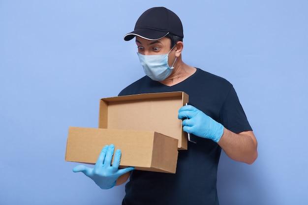 Beeld van de jonge geschokte mens het stellen met geopend pakket in handen, kijkend daarin met verraste gelaatsuitdrukking, die beschermende handschoenen en masker draagt