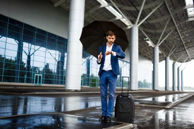 Beeld van de jonge koffer en de paraplu die van de zakenmanholding op horloge kijken die bij regenachtige post wachten