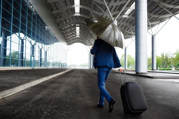 Beeld van de jonge koffer en de paraplu van de zakenmanholding bij regenachtige luchthaven