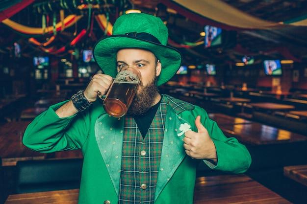 Beeld van de jonge mens in groen kostuum in bar het drinken bier van mok. hij houdt een grote duim op.