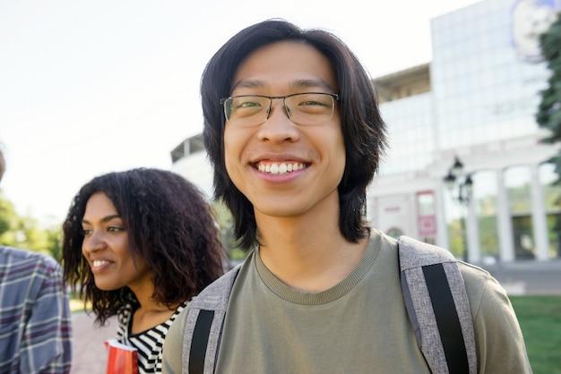 Beeld van de jonge vrolijke studenten aziatische mens die zich in openlucht bevindt. camera kijken.