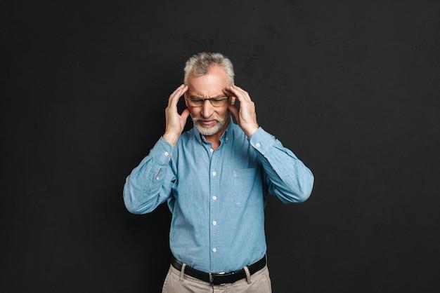 Beeld van de oude man 60s met grijs haar en baard met hoofdpijn en wrijven tempels in vermoeidheid, geïsoleerd over zwarte muur