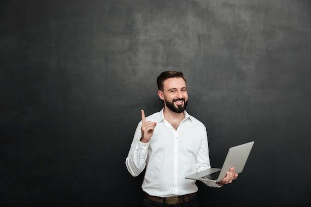 Beeld van de slimme donkerbruine mens die in bureau werkt dat het zilveren laptop gebaren met omhoog vinger gebruikt, dat over donkergrijze muur wordt geïsoleerd