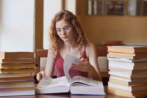 Beeld van doordacht hardwerkend jong meisje dat pagina's van reusachtig boek omdraait, op zoek naar juiste informatie voor studieproject, zorgvuldig thuisopdracht doet.