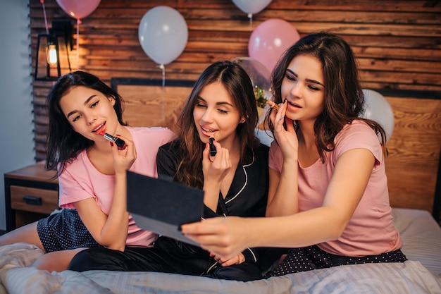 Beeld van drie tieners die make-up doen. ze doen wat lippenstift op de lippen en kijken in de spiegel. meisjes zijn geconcentreerd. ze zitten op bed in feestelijke kamer.