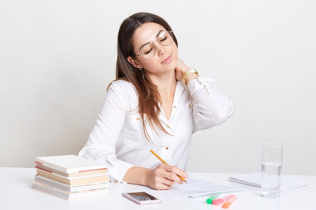 Beeld van drukke vrouw houdt hand op nek, voelt zich moe na lang werken met documenten, zit op werkplek, schrijft creatieve ideeën voor publicatie, heeft ogen gesloten, wacht op telefoontje op mobiele telefoon