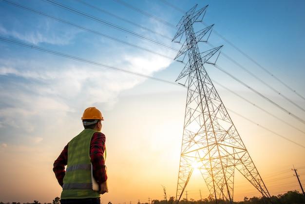Beeld van een elektrotechnisch ingenieur die en zich bij de stroompost bevindt bekijkt om het planningswerk te bekijken door elektriciteit bij hoogspanningselektriciteitspolen te produceren.