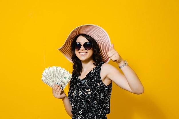 Beeld van een glimlachende bos van de meisjesholding van geldbankbiljetten en het tonen van ok gebaar dat over gele muur wordt geïsoleerd