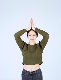 Beeld van een jong ontspannen vrouwenmodel dat handen boven het hoofd samenbrengt.