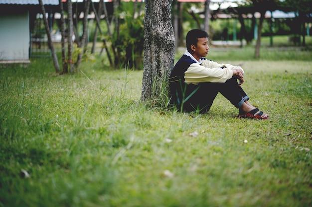 Beeld van een jonge jongen helaas alleen zitten in het bos depressie concept
