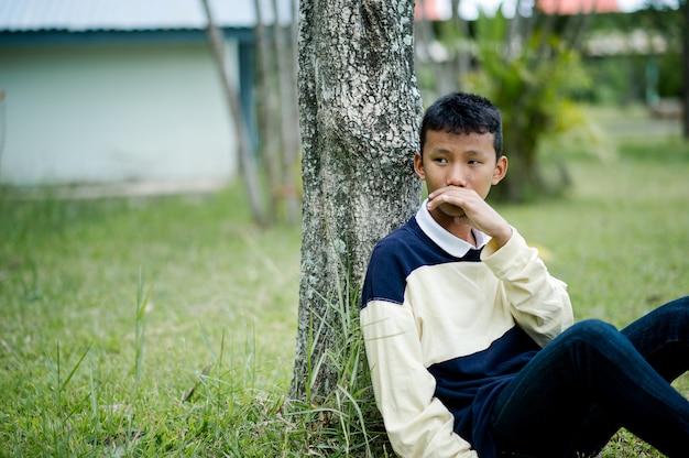 Beeld van een jonge jongenszitting die op iemand wachtend concept wachten