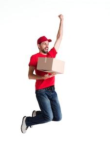 Beeld van een jonge leveringsmens die en doos springt houdt