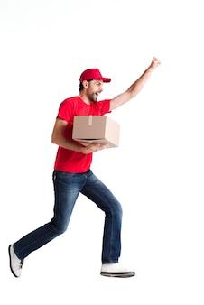 Beeld van een jonge leveringsmens die gelukkig met een doos loopt