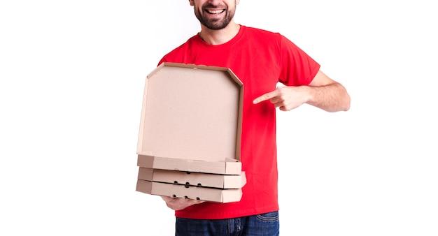 Beeld van een jonge leveringsmens die pizzadozen toont