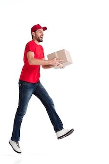 Beeld van een jonge leveringsmens die zijdelings met een doos loopt