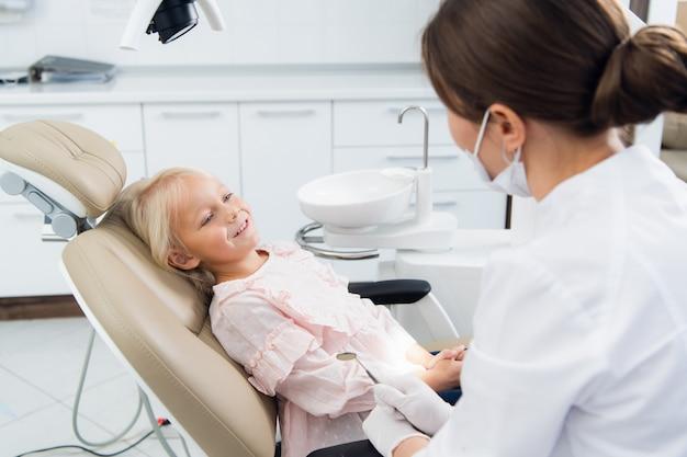 Beeld van een klein meisje die haar tanden laten controleren door een arts