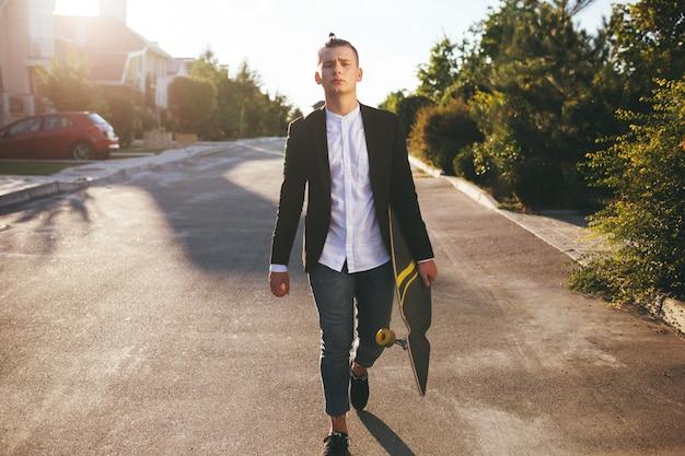 Beeld van een man met longboard die op weg gaat