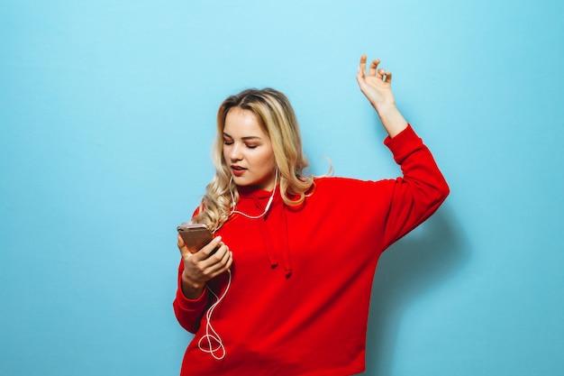 Beeld van een mooi blond opgewekt meisje dat aan muziek in hoofdtelefoons luistert en over blauwe muur danst
