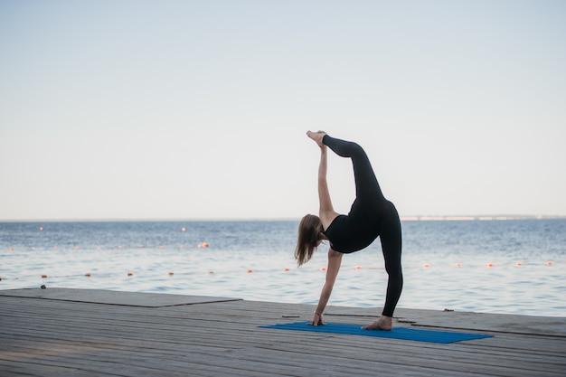 Beeld van een mooie vrouw die yoga doet bij het meer