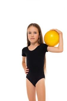 Beeld van een turnermeisje in witte korte sokken en zwarte trico volledige hoogtetribunes met gele bal in haar handen die op een witte achtergrond wordt geïsoleerd
