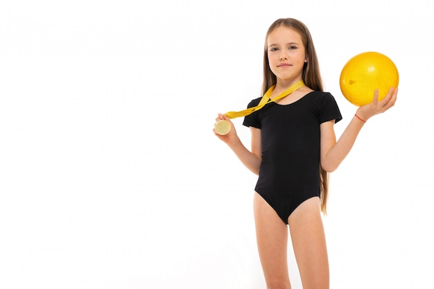 Beeld van een turnermeisje in witte korte sokken en zwarte trico volledige hoogtetribunes met gele bal in haar handen en een medaille om haar hals die op een wit wordt geïsoleerd