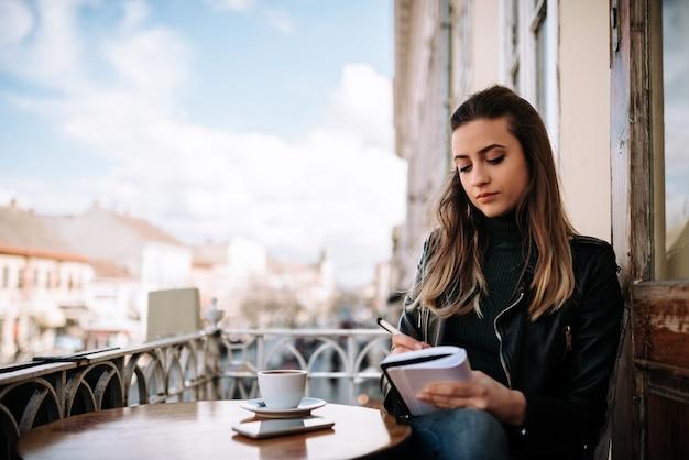 Beeld van een vrouwelijke journalist die terwijl het genieten van van een kop van koffie op een balkon in de stad schrijft.