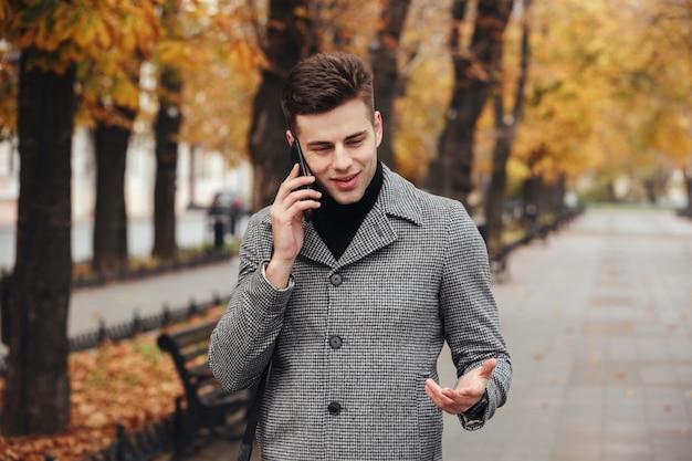 Beeld van elegant mannetje in laag die in leeg park met de herfstbomen lopen, en op smartphone spreken