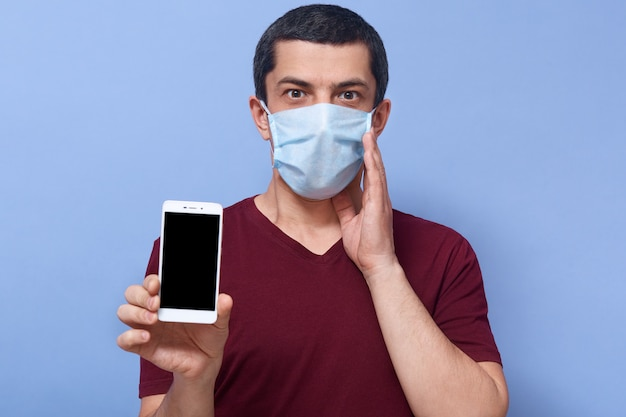 Beeld van emotionele geschokte kerel die één hand dicht bij gezicht plaatst, zijn smartphone houdt, in paniek is, apparaat gebruikt, thuis blijft, bang door coronavirus. mensen en pandemie concept.