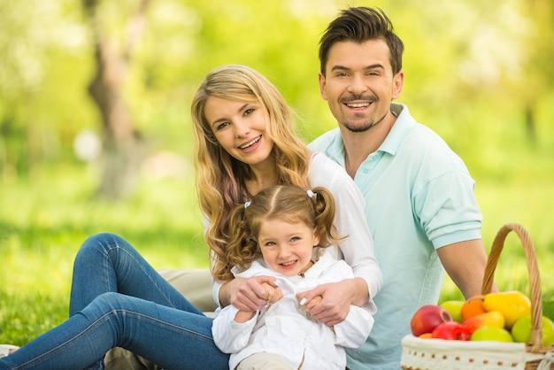 Beeld van gelukkig jong gezin met picknick in hout.