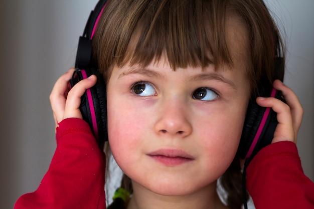 Beeld van gelukkig mooi kindmeisje met grote hoofdtelefoons bij