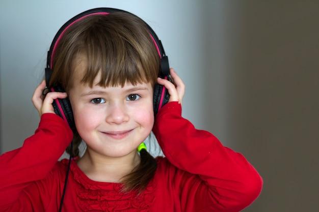 Beeld van gelukkig mooi kindmeisje met grote hoofdtelefoons thuis. blij kindmeisje die aan muziek op grijs vaag huis, technologie en muziekconcept luisteren.