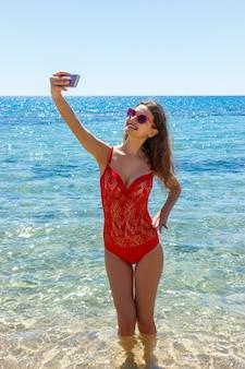 Beeld van gelukkige glimlachende vrouw gebruikend telefooncamera en makend selfie
