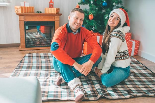 Beeld van gelukkige jonge paarzitting samen op deken. ze glimlachen en kijken naar de camera.