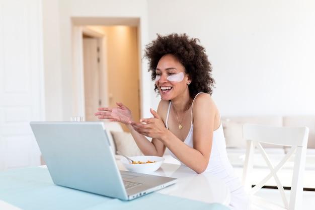 Beeld van gelukkige jonge verbazende vrouwenzitting binnen bij de lijst met laptop die cornflakes houden.