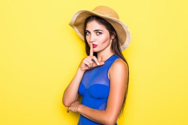Beeld van gelukkige jonge vrouw in blauwe swimwear geïsoleerd over gele muur.