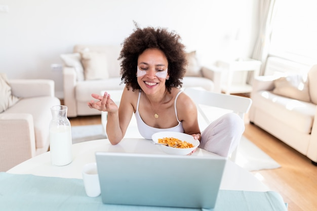 Beeld van gelukkige jonge vrouwenzitting binnen bij de lijst met laptop holdingscornflakes.