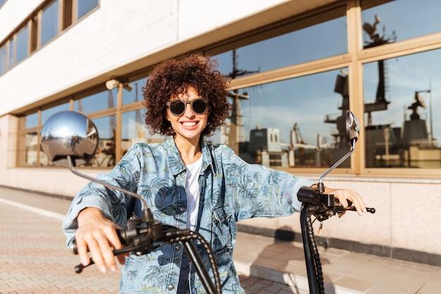 Beeld van gelukkige krullende vrouw die in zonnebril op moderne motor in openlucht zitten
