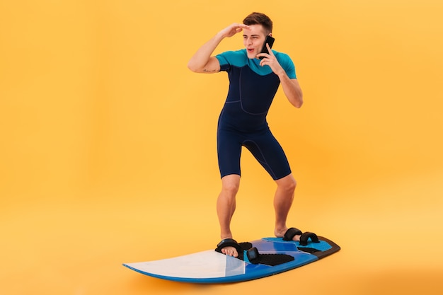 Beeld van gelukkige surfer in wetsuit die surfplank zoals op golf gebruikt terwijl het door smartphone spreekt en weg kijkt