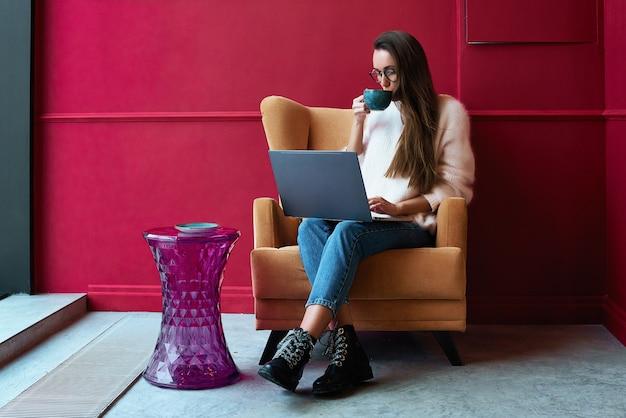 Beeld van gelukkige vrouw die laptop met behulp van terwijl het zitten bij koffie.