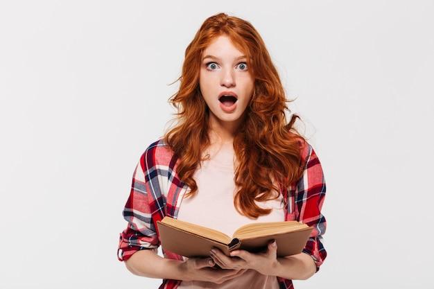 Beeld van geschokte gembervrouw in het boek van de overhemdsholding