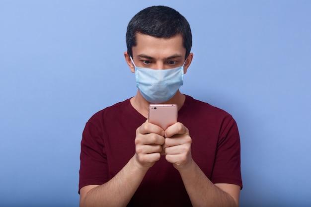 Beeld van geschokte nieuwsgierige kerel die mobiele telefoon in beide handen houdt, nieuws controleert, inhoud zoekt, in paniek is, informatie over covid19 leest, antibacterieel masker draagt. coronavirus concept.