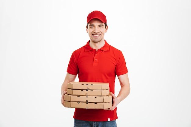 Beeld van glimlachende bezorger in rode t-shirt en glb-holdingsstapel pizzadozen, dat over witte ruimte wordt geïsoleerd