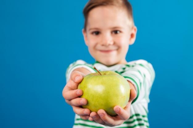 Beeld van glimlachende jonge jongen die appel geeft