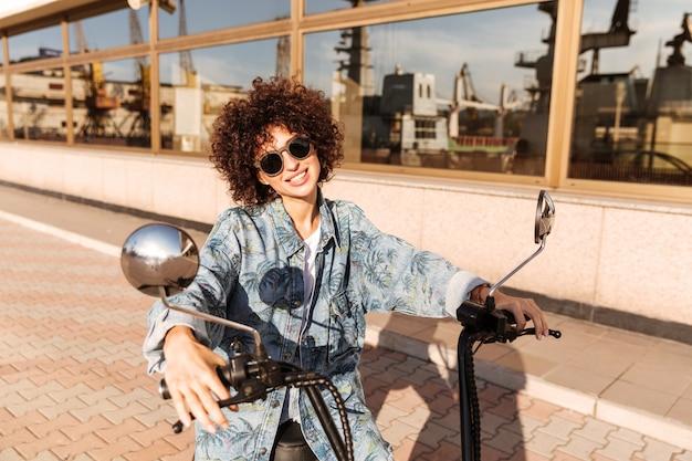 Beeld van glimlachende krullende vrouw die in zonnebril op motor zit
